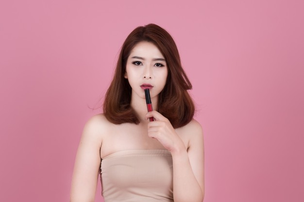 beautiful-woman-applying-lips-makeup-with-cosmetic-brush-on-isolated-pink-pastel-background_1894-27