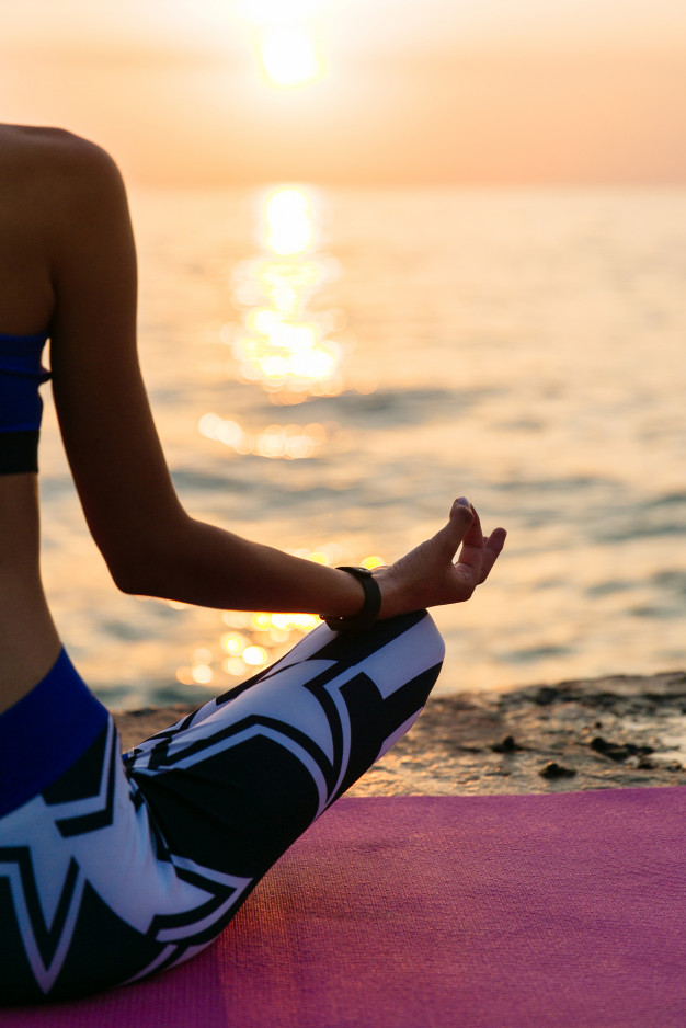 yoga-at-sunrise-back-view-of-a-half-body-of-sportive-woman-sitting-in-lotus-pose_8353-6933